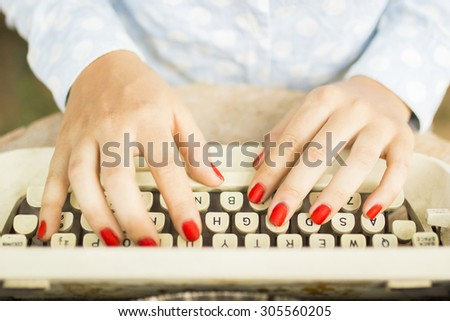 woman typing on a typewriter - stock photo