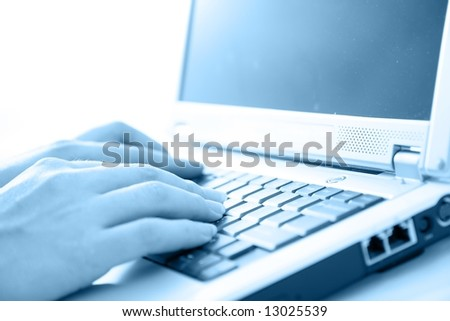 Woman typing on laptop.  High key, selective focus - stock photo