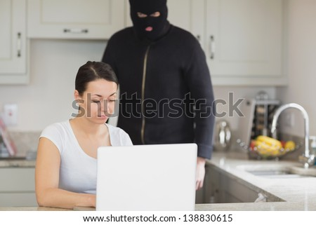 Woman typing on the laptop while burglar looking at it in kitchen - stock photo