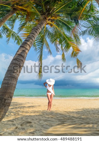 woman under palm tree  sea on backgroud