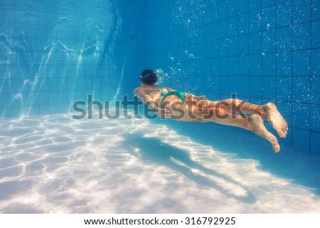 Woman underwater portrait wearing green bikini in swimming pool. Filtered image instagram style. - stock photo