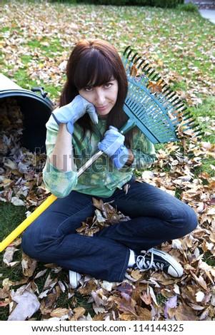 Woman Unhappy Raking Autumn Leaves - stock photo