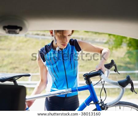 woman unloading blue road bike. Copy space - stock photo
