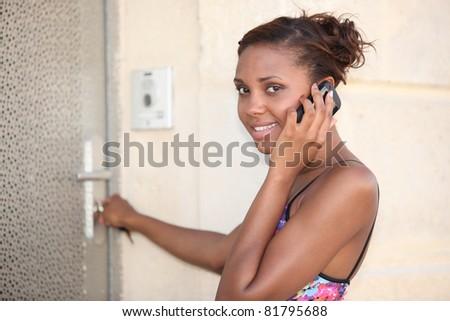 Woman unlocking her frontdoor - stock photo