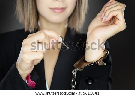 woman unlocking herself from handcuffs - stock photo