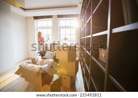 Woman unpacking lamp from moving box at new house - stock photo