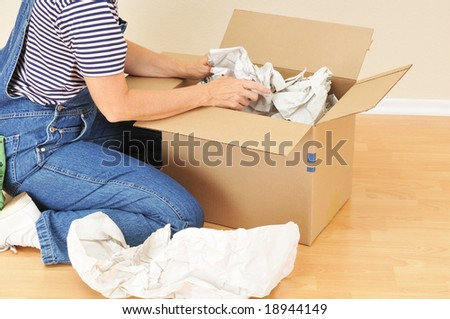 Woman unpacking moving box in an empty room - stock photo