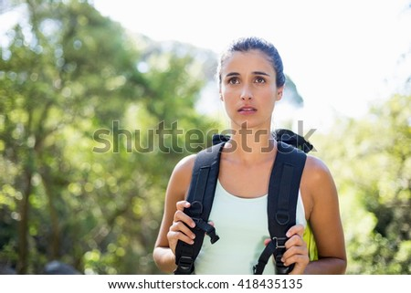 Woman unsmiling posing with her backpack on the wood - stock photo