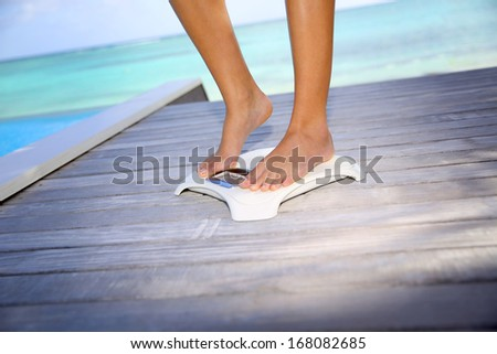 Woman up on scale to check on weight - stock photo