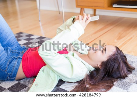 Woman updating her social networks while relaxing in the living room