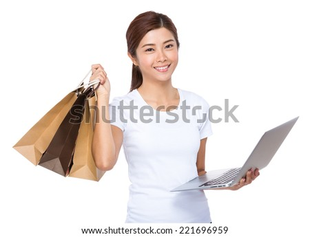 Woman use laptop and shopping bag - stock photo