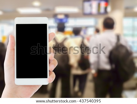 woman use mobile phone and blurred image of people in the airport terminal - stock photo
