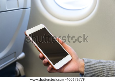 Woman use of cellphone inside air plane - stock photo