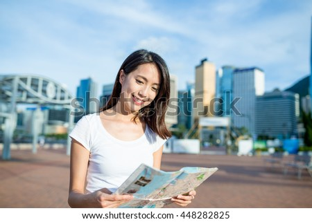 Woman use of city map in Hong Kong - stock photo