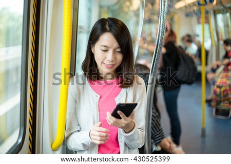 Woman use of mobile phone in train - stock photo