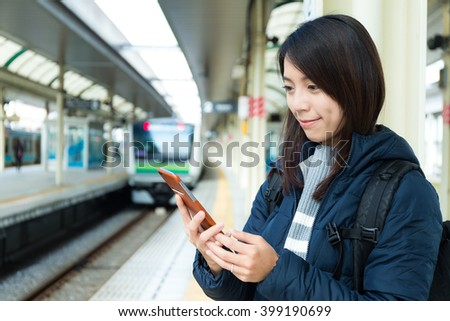 Woman use of mobile phone in trains station - stock photo
