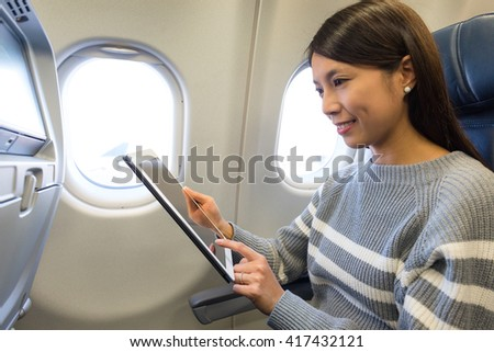 Woman use of tablet inside airplane - stock photo