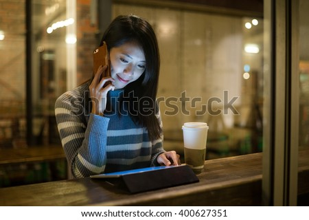Woman use of tablet pc and talk to cellphone in coffee shop - stock photo
