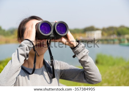 Woman use of the binoculars at forest