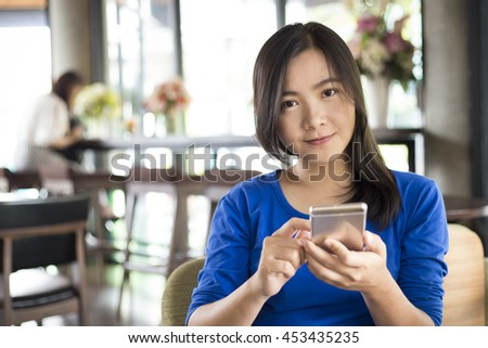 Woman use smart phone in cafe be happy
