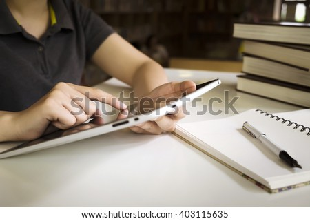 Woman use tablet for working, reading, communication, shopping. Young girl use tablet in library.  - stock photo