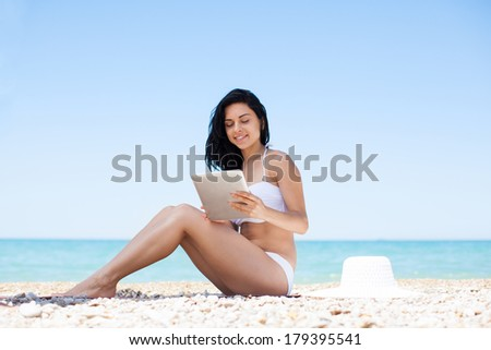 woman use touch pad tablet pc internet technology sitting beach, young girl summer travel ocean vacation - stock photo