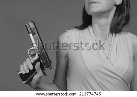 Woman uses a gun for self defense - stock photo