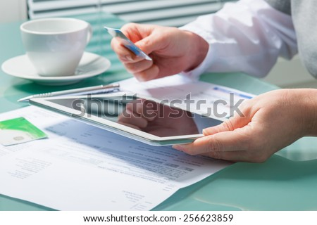 Woman using a credit card and digital tablet for buying on-line - stock photo