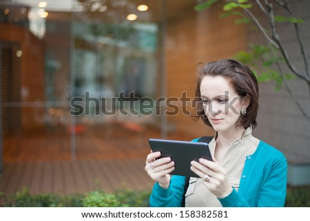 Woman using a digital tablet outside an office building in a city - stock photo