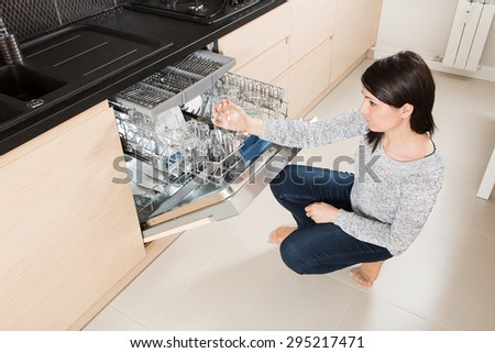 Woman using a dishwasher in a modern kitchen. Domestic appliance. - stock photo