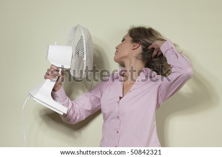 Woman using a fan to cool off - stock photo