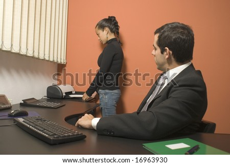 Woman using a fax machine while a businessman watches from his desk. Vertically framed photo. - stock photo