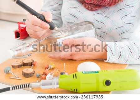 Woman using a high speed rotary multi tool to engrave ornament on the bottle - stock photo