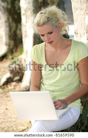 Woman using a laptop by a tree - stock photo