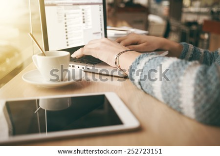 Woman using a laptop during a coffee break, hands close up - stock photo