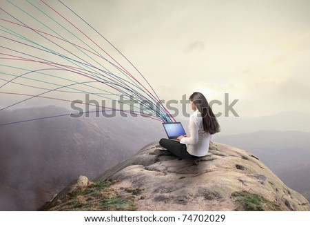 Woman using a laptop from a rock - stock photo