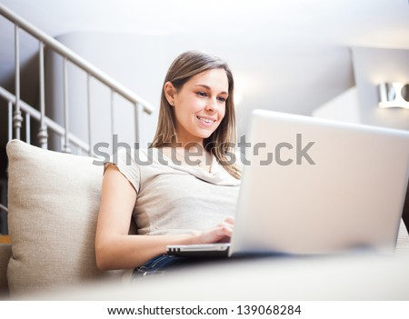 Woman using a laptop while relaxing on the couch