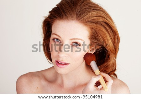 Woman using a large soft cosmetics brush to apply blusher under her cheekbone.