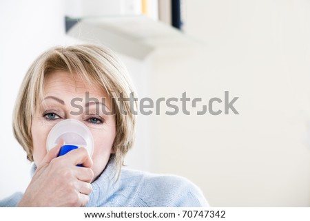 Woman Using A Nebulizer for respiratory treatment - stock photo