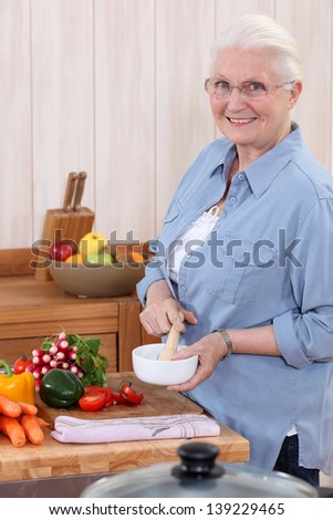 Woman using a pestle and mortar in the kitchen - stock photo