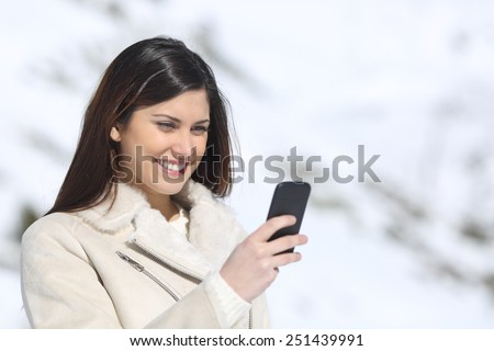 Woman using a smart phone on winter holidays with a snowy mountain in the background