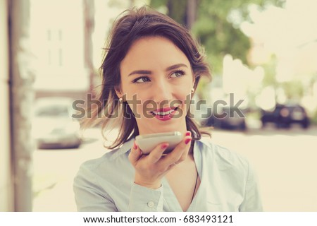 Woman using a smart phone voice recognition function online walking on a city street on a summer day