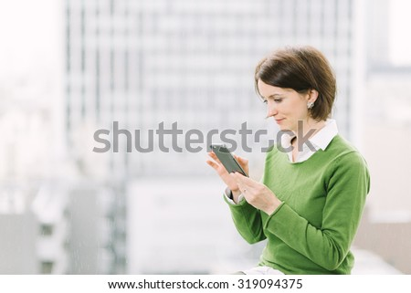 Woman using a smartphone in office by the window overlooking the business district with skyscrapers  - stock photo