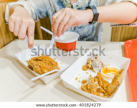 woman using a spoon to eat chicken.