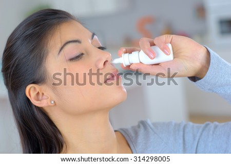 Woman using a spray for blocked nose - stock photo