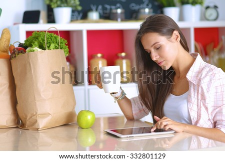 Woman using a tablet computer while drinking tea in her kitchen - stock photo