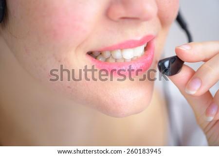 Woman using a telephone head set - stock photo