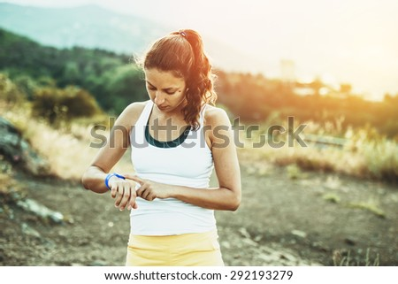 Woman using activity tracker or heart rate monitor. Outdoor fitness concept. Toned image - stock photo
