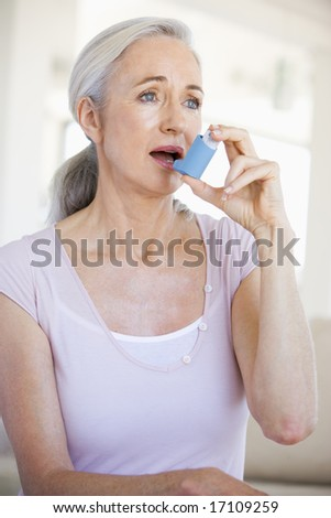 Woman Using An Inhaler - stock photo