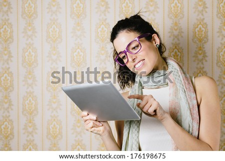 Woman using and reading on tablet pc. Brunette girl touching and looking to touch pad screen. - stock photo